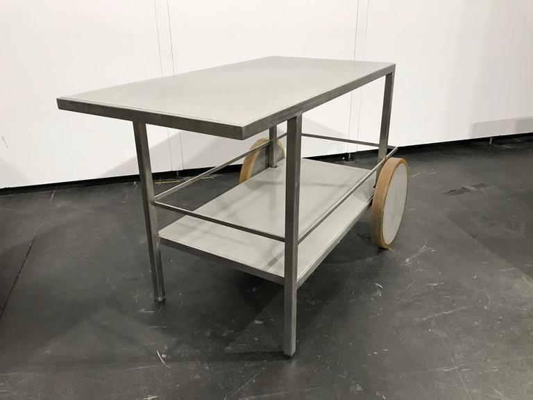 Clean and sleek bar cart made of brushed stainless steel and concrete. Suitable for indoor and outdoor use.