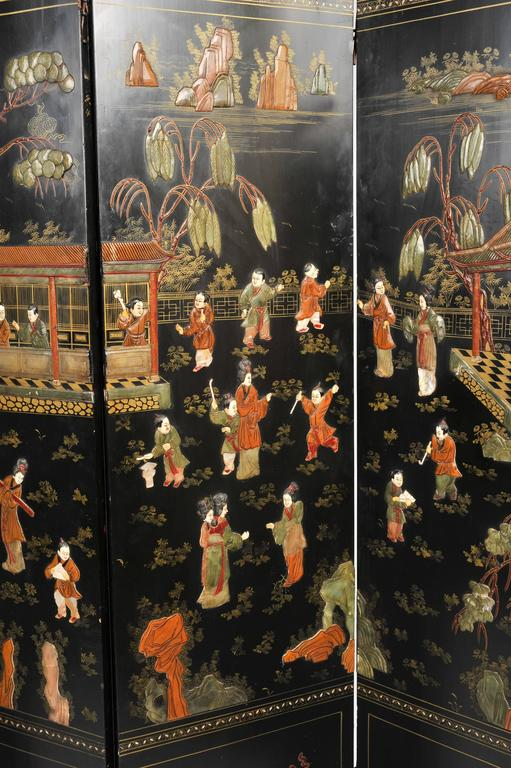 This exquisite and highly ornate 19th century black lacquer Chinese folding screen features 6 panels, each depicting parts of a large outdoor scene of various men and women performing various tasks around a large central house. The design and all