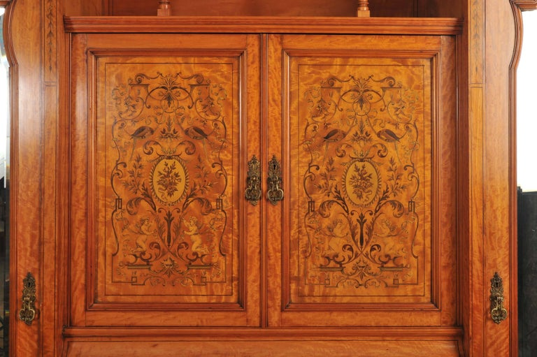 This magnificent late 19th century English satinwood wardrobe features an ornate inlay work of floral, cupid and parrot designs surrounded by swags and scrolls. The wardrobe is grand in size and of exceptional quality. Each side has hooks for