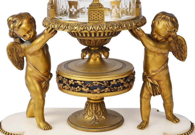 A very good quality late 19th century Louis XVI style ormolu and cut-glass revolving mantel clock. Having cherubs on either side support the glass case with classical gilded ormolu swags and foliate decoration. Revolving enamel numerals to the clock