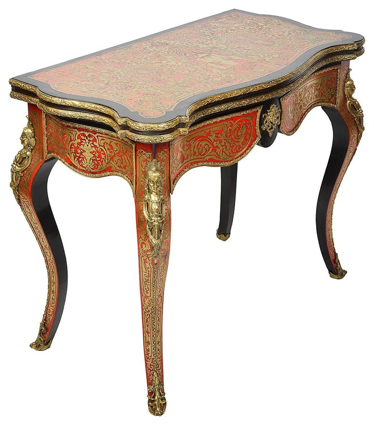 A good quality 19th century French Boulle inlaid card table, having gilded ormolu mounts, classical scrolling inlay with figures in the centre, opening to reveal a green baize card playing surface. Raised on elegant cabriole legs, terminating in