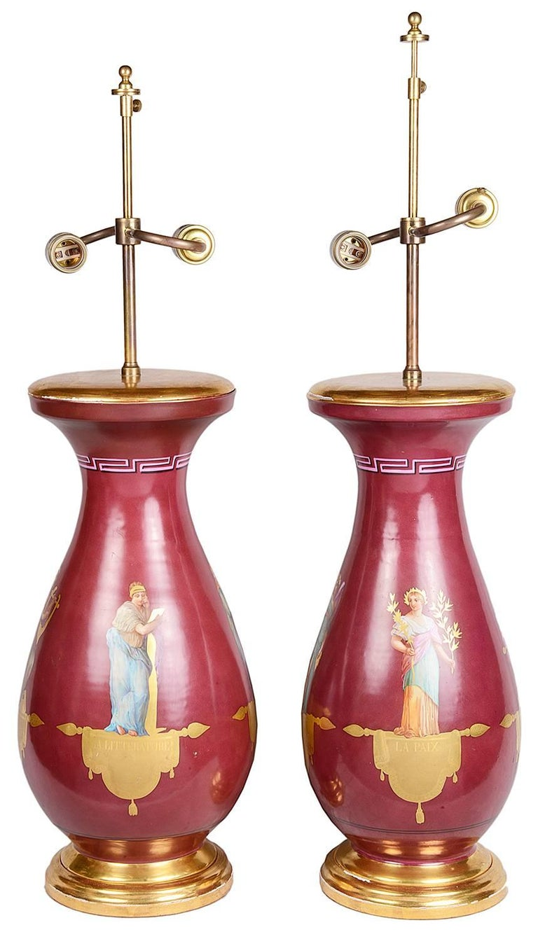 A very good quality pair of 19th century Paris porcelain vases or lamps. Each depicting classical Roman figures with a burgundy ground.