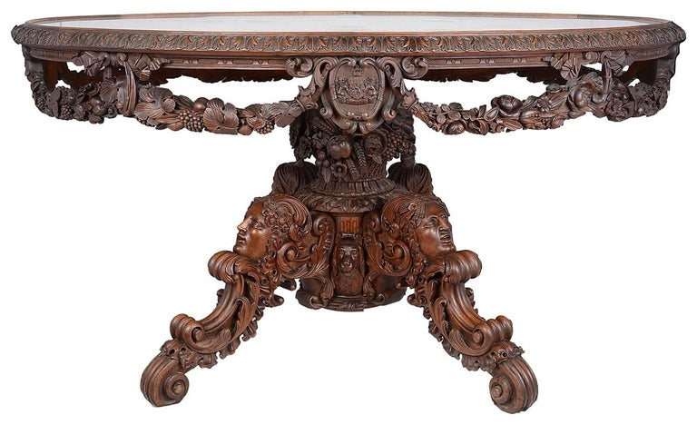 A Victorian carved walnut and marble mounted centre table, circa 1860, the oval grey veined white marble top within a repeated acanthus carved edge, the pierced frieze decorated with fruiting branch swags interspersed with armorial shields, one