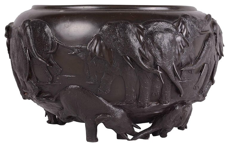 A fine quality late 19th century Meiji period (1868-1912) Japanese bronze jardiniere, depicting roaming elephants in relief.