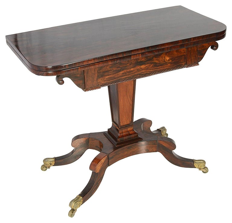 A good quality pair of Regency period rosewood card tables, circa 1820. Each with tops that unfold to reveal a tooled leather cover card play top. Raised on central square tapering pedestals and four splay bases that terminate in the original