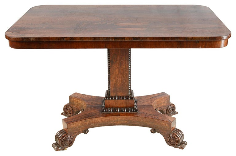 A good quality Regency period rosewood breakfast table, raised on a square section pedestal, platform base with carved scrolling feet.