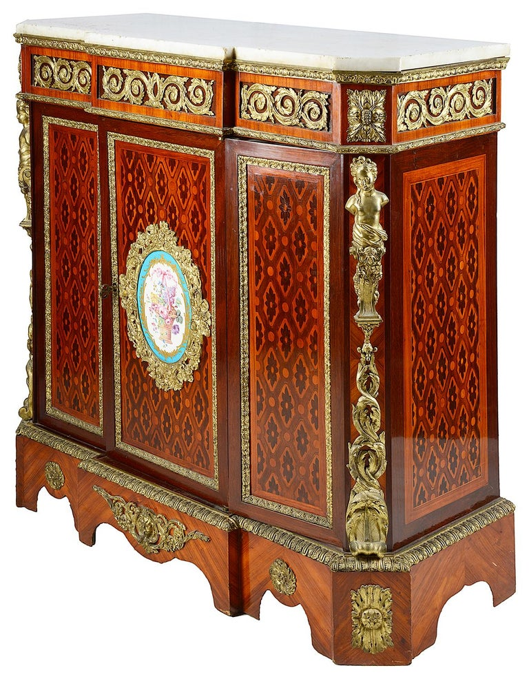 A good quality late 19th century side cabinet, having a white marble top, gilded ormolu scrolling mounts to the frieze, various exotic woods to the parquetry and marquetry inlay, a Sevres style porcelain plaque with flowers in a basket to the
