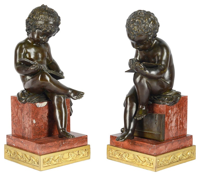 A fine quality pair of 19th century classical bronze seated putti, reading and writing, mounted on square rouge marble plinths and engraved gilded ormolu bases.