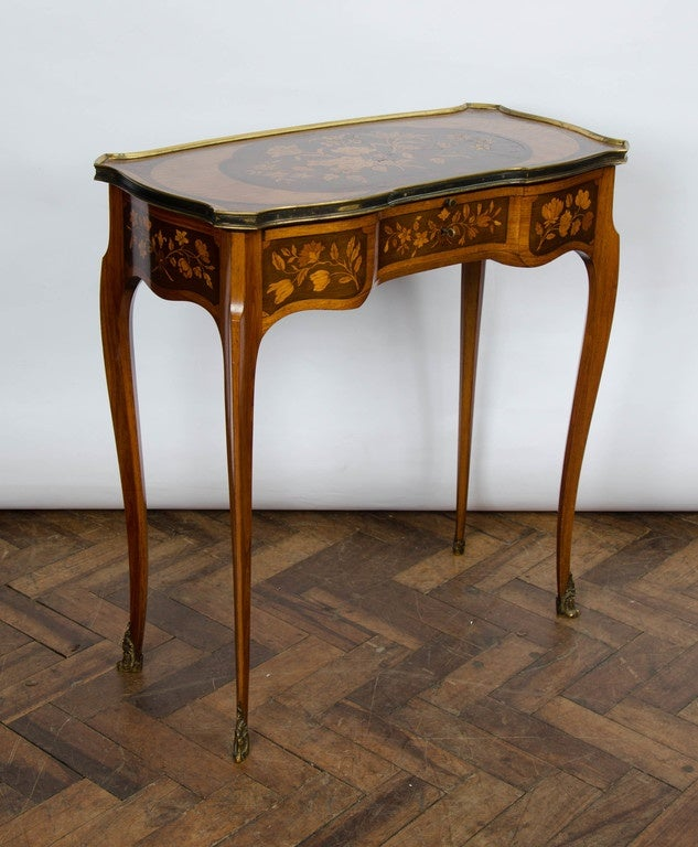 A very good quality pair of French Louis XV style marquetry inlaid side tables, Having three drawers to each, the central drawer revealing a hinged mirror. A slide above the drawers with an inset leather top. Raised on delicate cabriole legs,