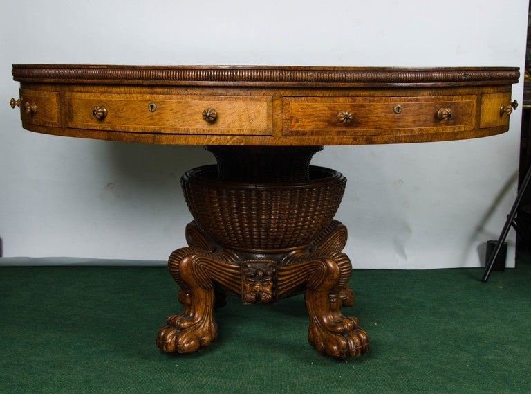 A rare and striking Regency period Pollard Oak drum table, having a segmented top with brass inlaid crossbanding, the frieze drawers each with Bramah locks and carved melon like knob handles. Raised on this wonderfully carved centre pedestal with