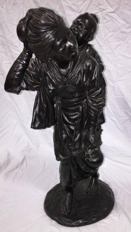 A very good quality 19th century Meiji period (1868-1912) Japanese bronze study of a mother carrying her child. Each wearing classical dress, signature to base.