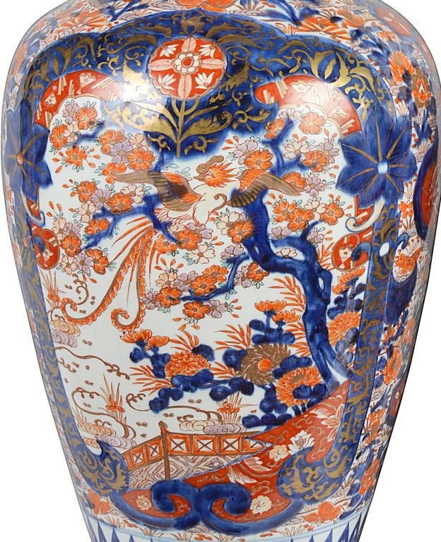 A large, impressive and decorative pair of 19th century Japanese Imari vases. Each depicting classical motifs, exotic birds, flowers and trees in the Classic Imari blues and oranges.