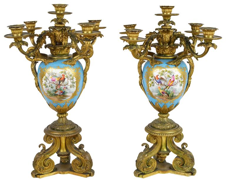 A very impressive pair of French 19th century sevres porcelain and gilded ormolu candelabra. Each candelabra having five branches with scrolling leaf decoration. The turquoise porcelain vases having hand-painted panels of exotic birds with gilded