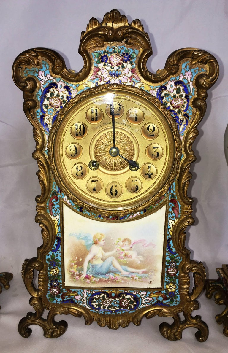 A very good quality late 19th Century French Louis XVI style Champleve enamel clock set. The clock having a classical scene of a cherub handing flowers to a young maiden. the boarder of the clock having wonderful colored enamel set in an gilded