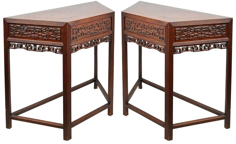 A good quality pair of late 19th century Chinese hardwood console tables, each with carved blind fretwork and pierced, reeded decoration to the legs and a single drawer. Having a stretcher to each of the bases.