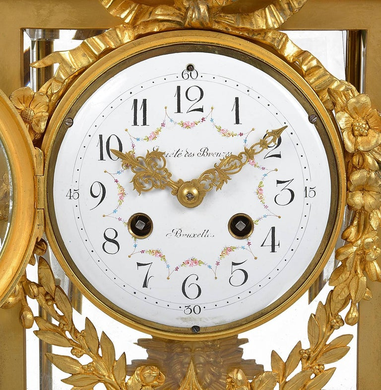 A good quality 19th century French gilded, Louis XVI style ormolu mantel clock. Having a gilded wreath and arrow sheath above a white marble top, ormolu four glass case, with a white enamel clock face, an eight day striking movement, flower and