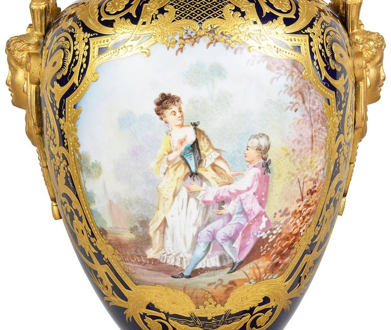 A very good quality late 19th century French 'Sèvres' lidded vase. Having gilded ormolu-mounted to the cobalt blue background with scrolling gilded decoration. The painted panel to the front depicting a classical romantic scene.