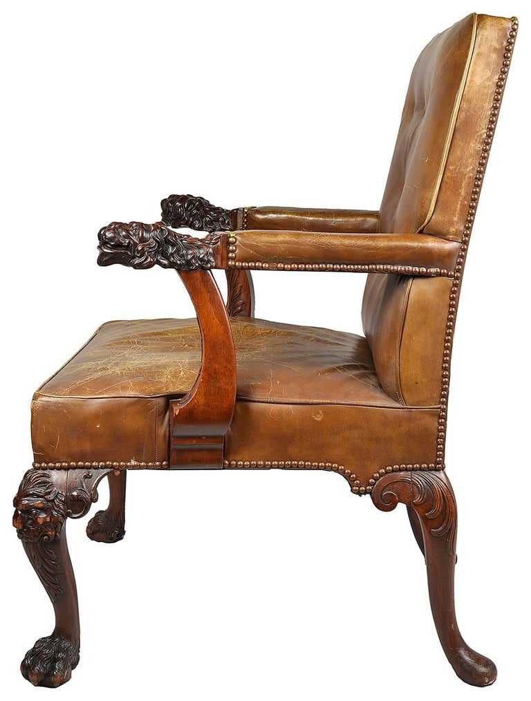 A very good quality late 19th century Chippendale influenced mahogany desk / armchair. Have wonderful faded leather upholstery. Carved mythical lion masks to the arm rests and raised on carved Lion mask cabriole legs terminating in carved claw feet.
