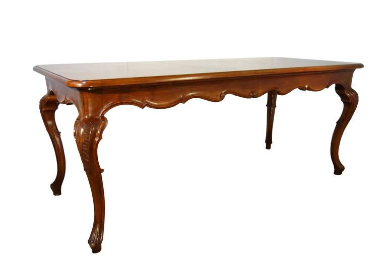 Elegant, long walnut table with shaped cabriole legs and shaped skirt, beautifully carved details, late 19th century.