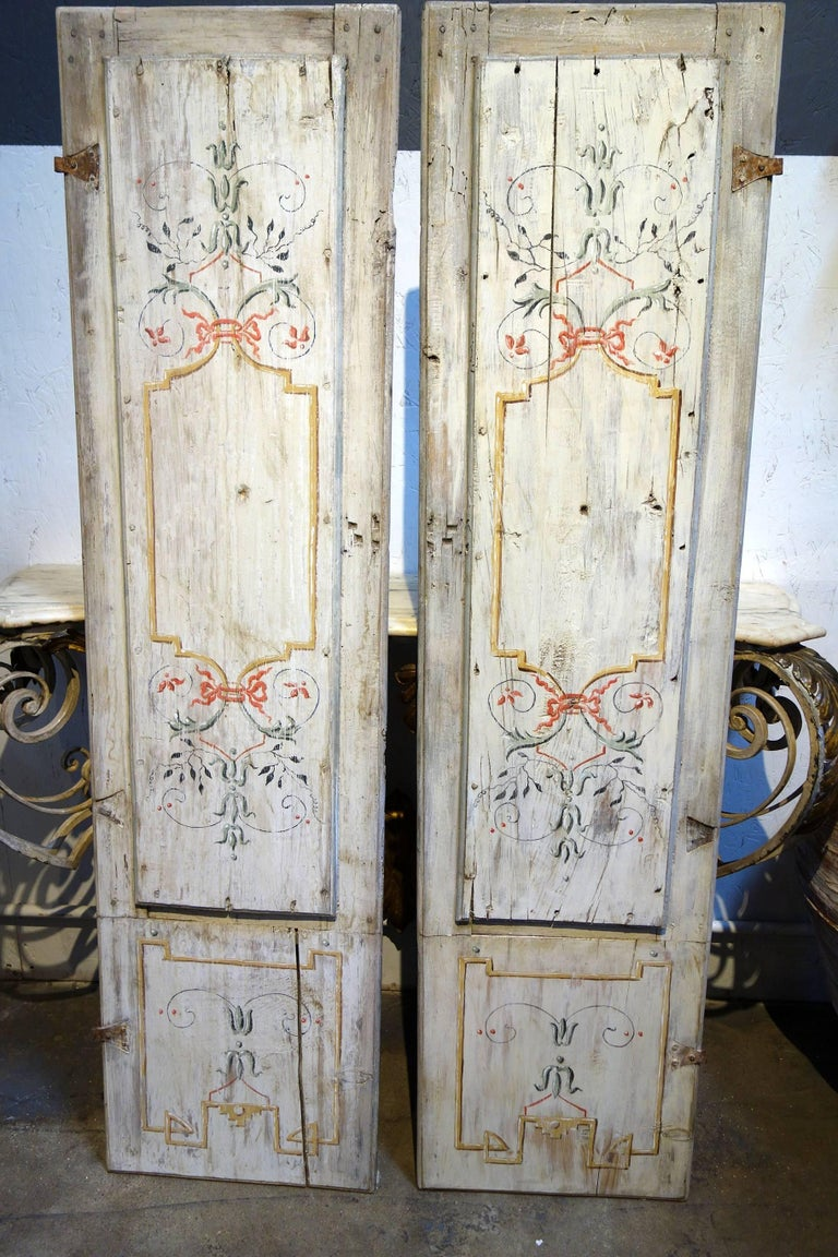 """Lovely pair of hand-painted door panels with iron hinges. Well preserved old structure. Early 19th century.  Measures: 64"""" H, 16.75"""" W each panel, paired 33"""" W, 1.5"""" D."""