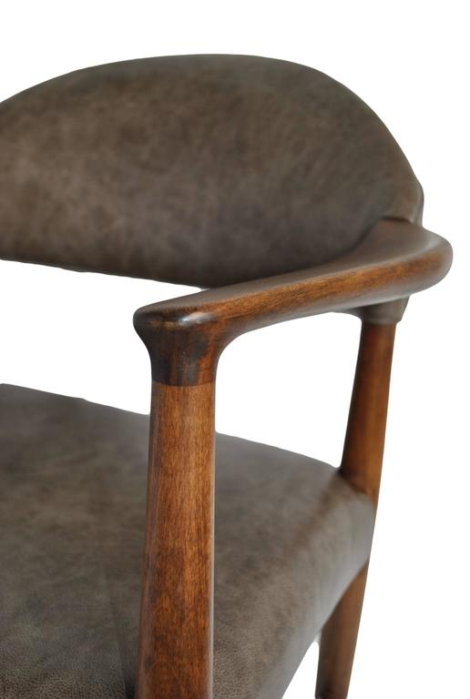 A Classic Kurt Olsen elbow chair fully refurbished and professionally reupholstered in new Italian leather upholstery. Produced in Denmark, circa 1950s. Dark original stained beech polished frame.