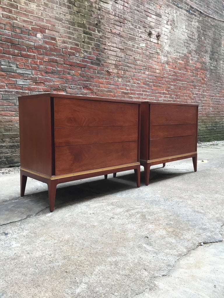 Pair of teak with brass detail three-drawer dressers retailed for John Stuart. True sign of quality when a piece of furniture has the John Stuart medallion in the top drawer. Warm teak with brass detail around the base. Featuring solid tapered legs