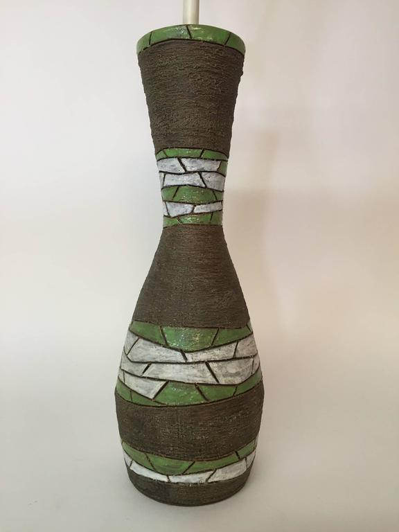 Curvaceous art pottery lamp for Raymor. Designed by Aldo Londi for Bitossi, circa 1950-1960. Glazed in matte brown and gloss white and green.  The pottery measures 17.75