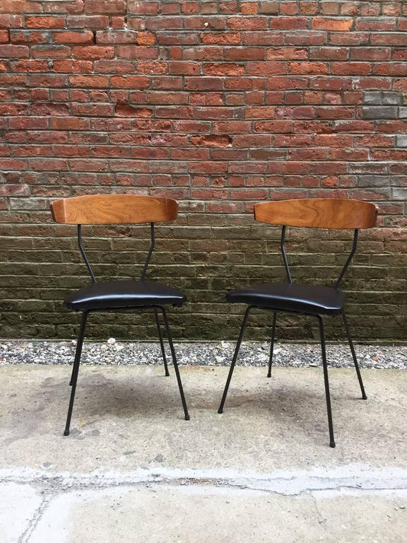 The pair of chairs is a great variation to the Pascoe design; the backs are angled in and the seat cushions are flush mounted to the base. Iron bases with bentwood walnut veneer back supports.