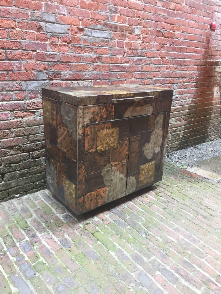 Designed by Paul Evans for Directional. Patchwork mixed metals cabinet consisting of Copper, Brass and Pewter. Black interior with flip-top and two cabinet doors with shelves. On casters, circa 1971.  Measures: 36.25