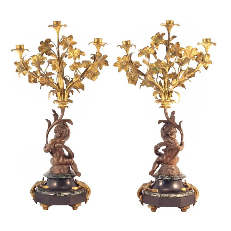 A pair of late 19th century Louis XVI style candelabra, featuring a marble base, cast bronze putti and gilt floral branches.
