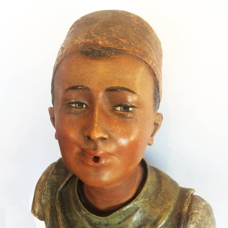 Art Deco bust in painted terracotta, advertising Turkish cigarettes. Finely detailed and in polychrome colours, with traditional Fez (hat) with black tassel falling to the rear, all on a black,