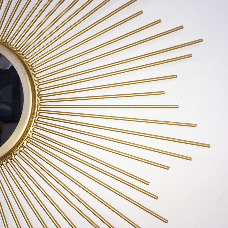 Midcentury sunburst shape, flat mirror with gilt tapered solid rods creating a star shape. The rear is fitted with a tab, recessed to take a simple wall screw or nail to hang the mirror. This piece is totally perfect with no damage or repairs. The