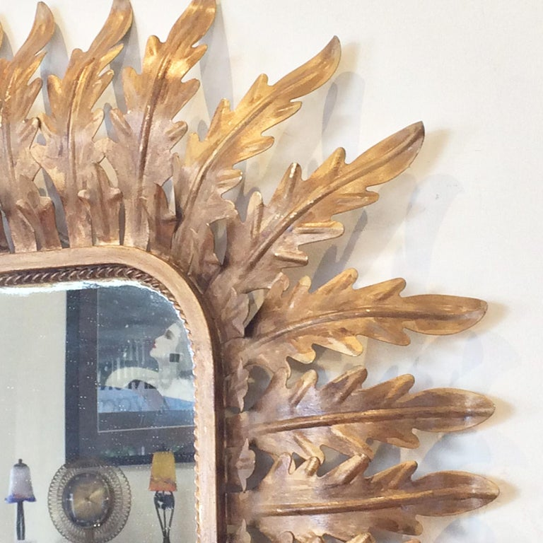 Art Deco mirror, within a very old metal frame of gilt acanthus leaves, and other trim details. The outer perimeter has curved acanthus leaves holding the mirror outward, off the wall behind. The leaves then surround a rectangular edge, and finally