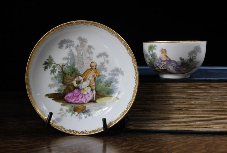Meissen teabowl and saucer, superbly painted with large-scale Watteauesque scenes of couples in garden, within a fine gold tracery border. 