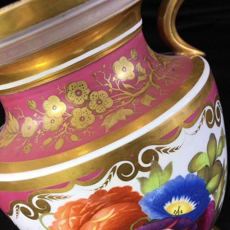 English bone china urn, the form taken from a Greek neck-Amphora, the gilt handle terminals with scrolls framing a face, the front with a panel of flowers reserved on a puce ground, the reverse with superb tooled gold flower spray with tooling.