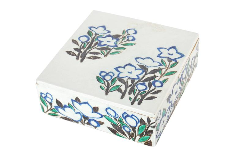 Japanese pottery covered box in the style of Ogata Kenzan, with a freely brushed design of flowers spread across its sides in tones of black, blue and green, Taisho period, circa 1920  Signature to base (not yet translated)  Dimensions: H 7.5cm x W