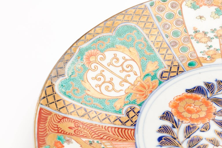 Pair of large antique Japanese Imari porcelain plates with gilded floral design in overglaze enamels, Meiji period, circa 1900.  The plates are decorated with chrysanthemums in the center and the surrounding panels are painted with maple trees,