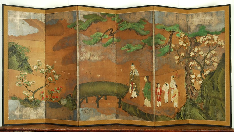 Japanese Kano school screen with pine tree, camellias, cherry blossom and Chinese figures in the landscape, circa 18th century.  Materials: Pigment colors and oxidized silver leaf on paper  Dimensions: H 170cm x W 373cm.