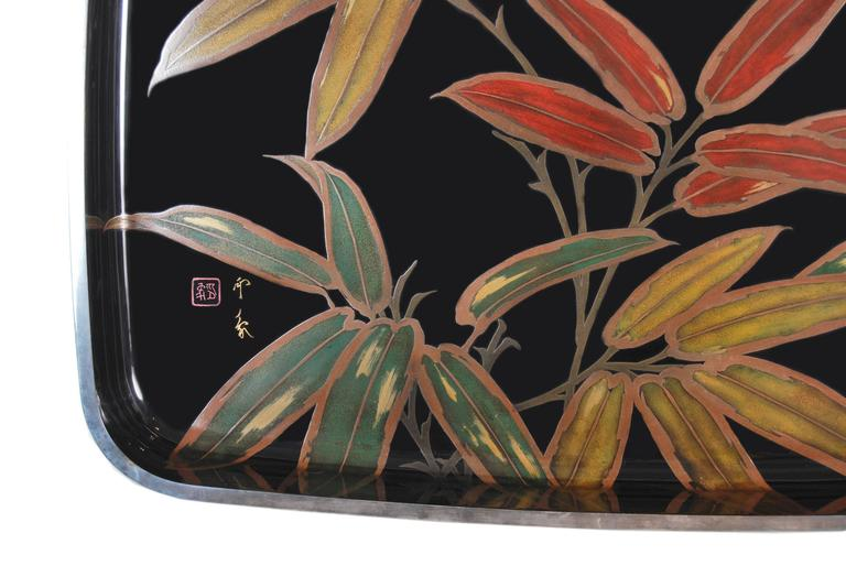 Japanese black lacquered tray of generous proportions with a bold design of bamboo leaves rendered in multicolored pigments and gold and silver maki-e lacquer. The top edge further decorated and protected by an applied solid silver rim, now