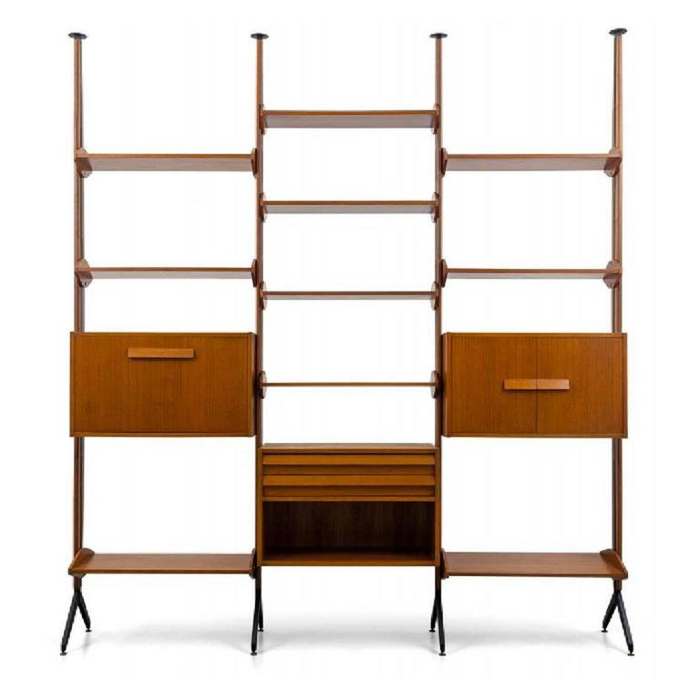 An architectural shelving system or room divider in teak and lacquered metal.  Italy 1960s.  The shelving comprises four uprights - which can be configured as two single bays, a double or triple - together with three cabinets and ten shelves.  The