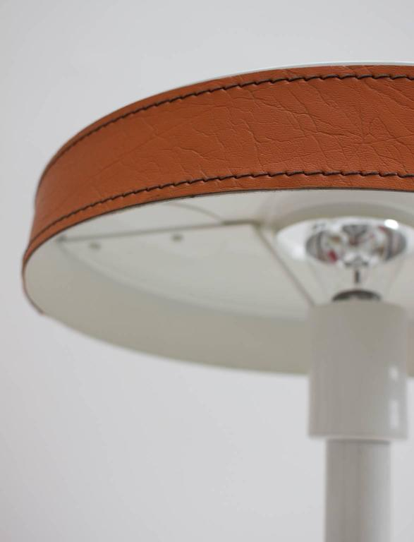 Modernist table lamp with leather details.  The striking design has a white enamelled aluminium body and shade, and wooden base, trimmed in Hermes-orange leather with heavy stitching; the base is covered with fine black leather. The shade attaches