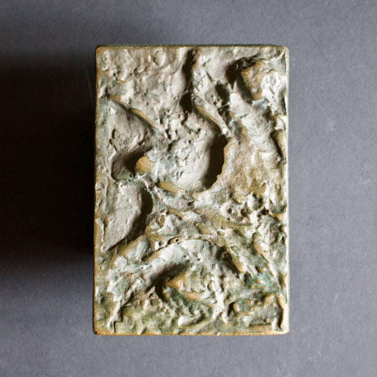 A single rectangular bronze door handle with abstract relief, evoking the textures and patterns of natural rock. Europe, mid-20th century.  The handle is in good original condition, and there are minor signs of old paint on the reverse which cannot