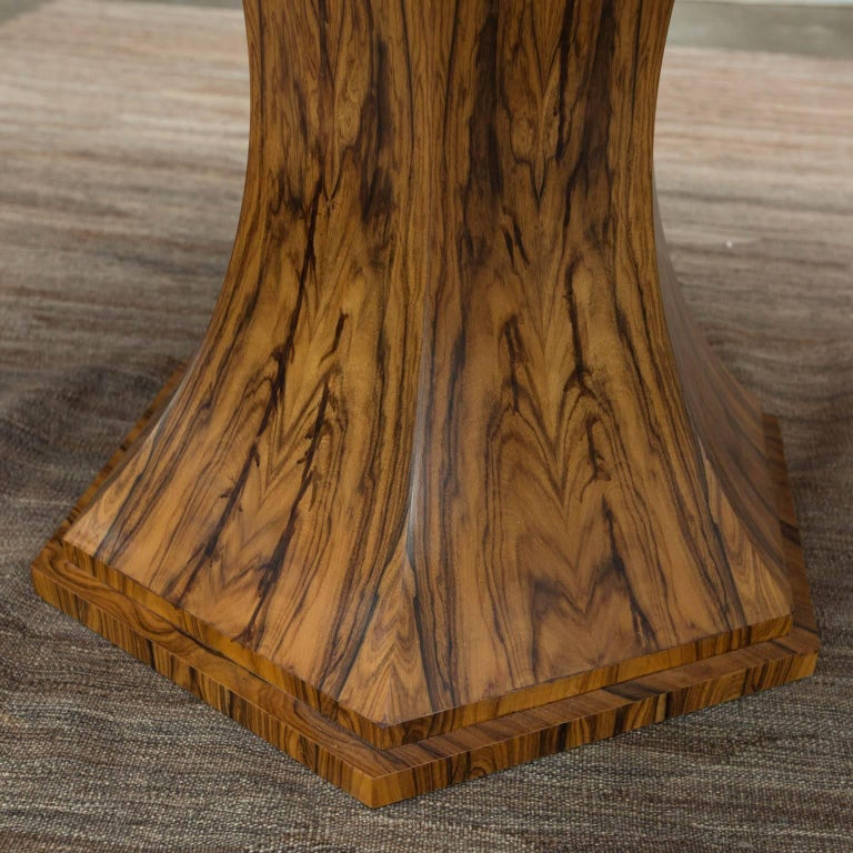 Elliptical shaped custom made table by award-winning furniture designer Gregory Clark. Formed from bookmatched Bolivian rosewood veneers atop a six sided base with matching veneers on each side.