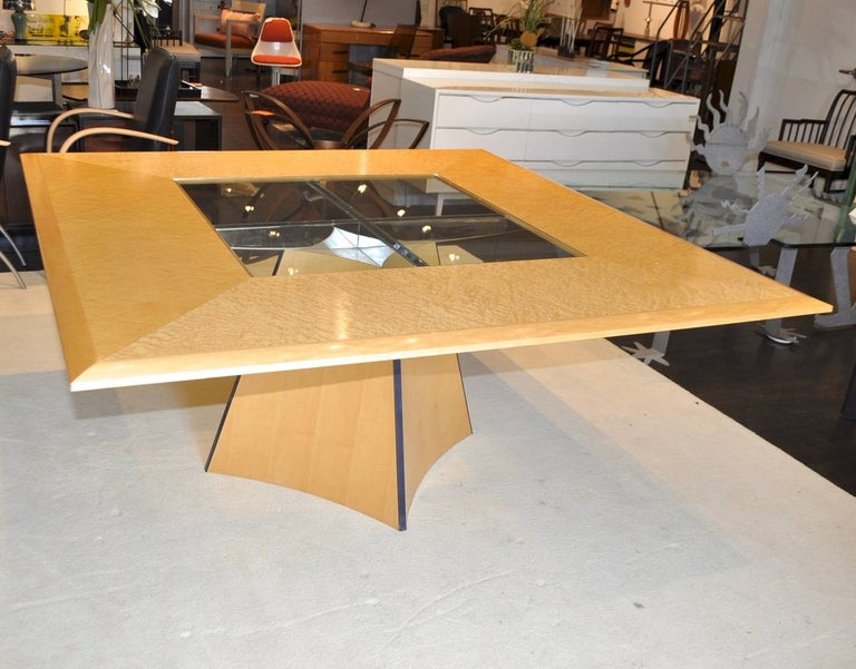 A striking square dining table for eight made from birds-eye maple veneers with polished chrome cross bars supporting a glass topped centre. Made by boutique cabinet makers Senior & Carmichael of Benchworth, England.