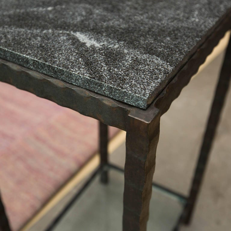 Compact but substantial side table made from hand forged patterned steel with a forged wave edged granite. Features a single glass shelf.