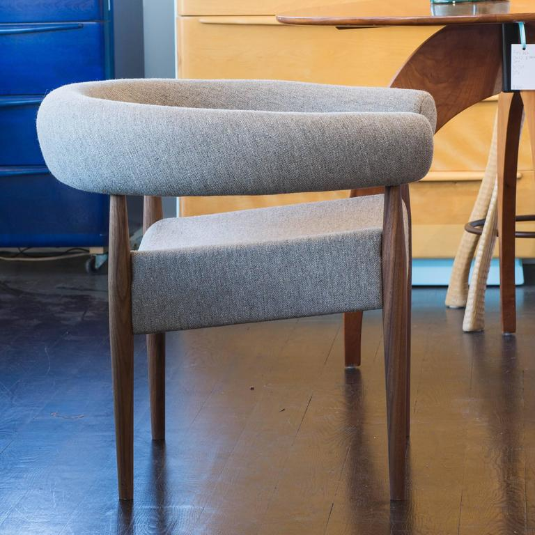 Designed in 1958 by the most prolific designer Denmark has probably ever produced, this is a brand new reproduction by the original manufacturer Getama. Walnut frame and beige cloth upholstery.