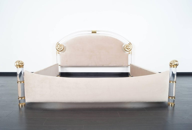 This glamorous vintage Lucite and brass king-sized bed was designed by Marcello Mioni. The bed is constructed with solid Lucite poles and large brass nautilus that gives the bed a unique design.