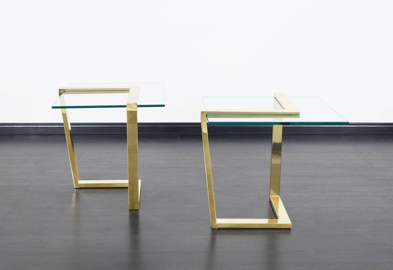 Elegant vintage brass cantilevered side tables manufactured by DIA (Design Institute of America), circa 1980s. These tables have a modernist design in which the architecturally constructed chevron-shaped polished brass bases stand out. The bases