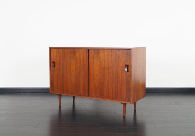 Vintage walnut sideboard designed by Stanley Young for Glenn of California. Features two sliding doors with sculptural pulls. Inside contains one adjustable shelf and four lacquer drawers.