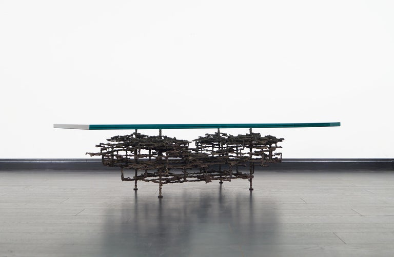 This exceptional vintage Brutalist bronze coffee table designed by Daniel Gluck for Daniel Gluck Studio. This stunning coffee table exposes an architectural sculptural design. Signed.